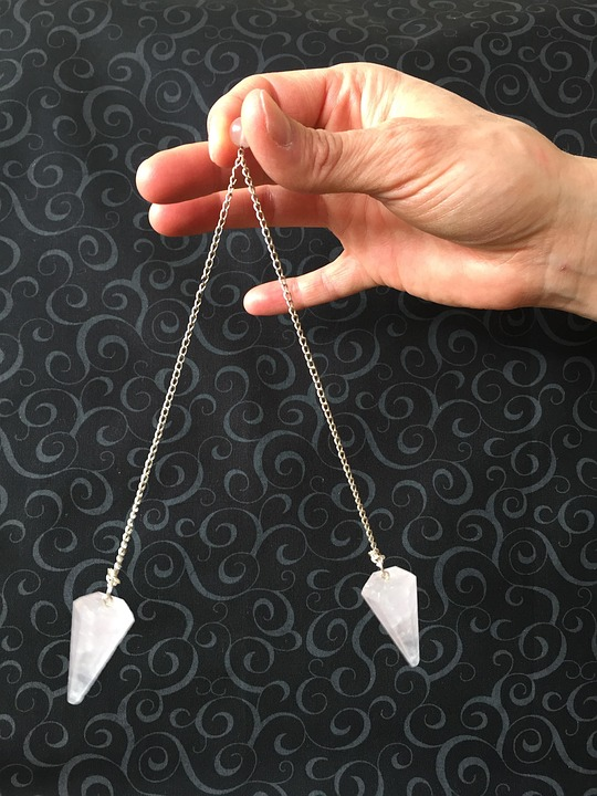 A man holding pendulums explaining what happens in hypnosis